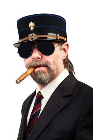 Closeup portrait of stilish man in   gendarme stile  hat and in sunglasses smoking cigar,serious photo