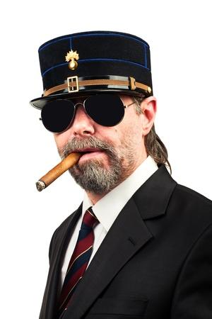 stilish: Closeup portrait of stilish man in   gendarme stile  hat and in sunglasses smoking cigar,serious