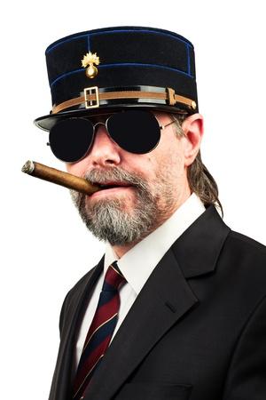 stilish: Closeup portrait of stilish man in   gendarme stile  hat and in sunglasses smoking cigar,