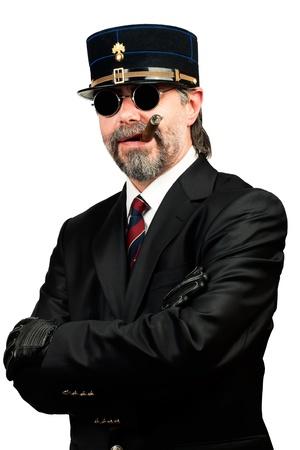 stilish: portrait of stilish man in   gendarme stile  hat and in sunglasses smoking cigar Stock Photo
