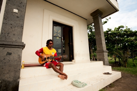 legian: BALI - DECEMBER 27: Unidentified balinese man plays guitar in Legian beach on December 27, 2012 in Bali, Indonesia. Legian is a suburban and beach area on the west coast of Bali.