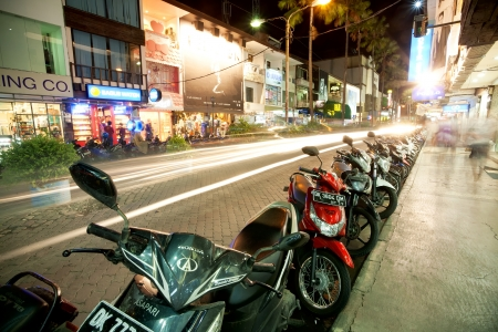 BALI - DECEMBER 27: Nighttime, mopeds stays in the parking at the shopping street, Kuta's area on December 27, 2012 in Bali, Indonesia. Kuta is known internationally for its long sandy beach, varied accommodation, many restaurants and bars.