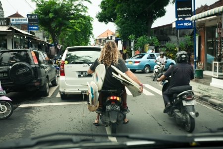 BALI - JANUARY 4 :  Tourist with surfboards on scooter on JANUARY 4, 2013, Bali, Indonesia. Due to heavy traffic and poor roads people choose scooters to get around the island. 新聞圖片