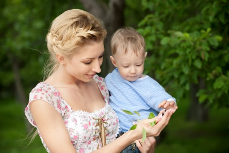 happy blond mom and one year old son enjoying nature together
