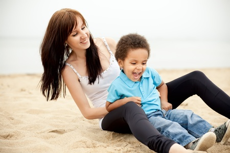 descend: Caucasian mother with a son of an african descend having fun together outdoors. Stock Photo