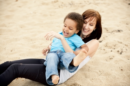 Caucasian mother with a son of an african descend having fun together outdoors. photo