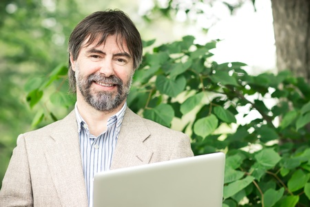 50 55: Portrait of happy middle-aged businessman holding notebook and smiling, outdoors Stock Photo