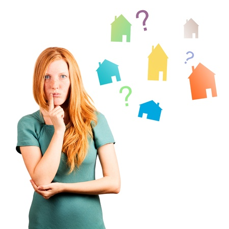 thinking red-haired girl isolated on a white, coloured houses and questions at background