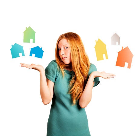 red-haired girl facing a choice isolated on a white, holding coloured houses at her hands  Stock Photo - 20535269