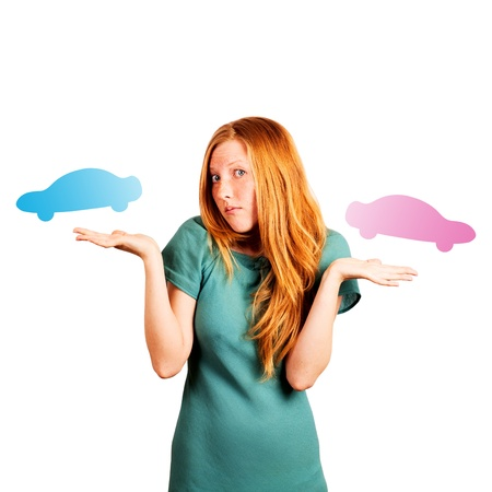 red-haired girl facing a choice isolated on a white, holding coloured cars at her hands