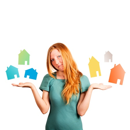 hesitations: red-haired girl facing a choice isolated on a white, holding coloured houses at her hands