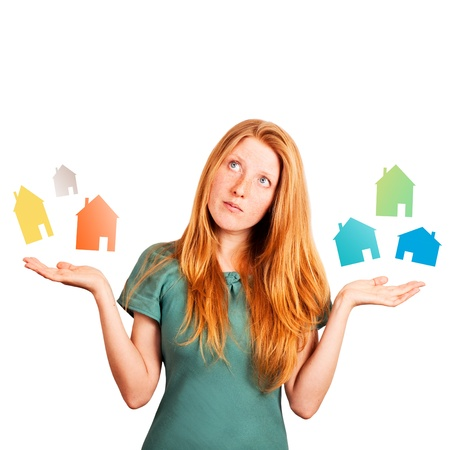 red-haired girl facing a choice isolated on a white, holding coloured houses at her hands  Stock Photo - 20535268