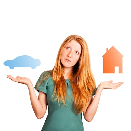red-haired girl facing a choice isolated on a white, holding coloured car and house at her hands  版權商用圖片
