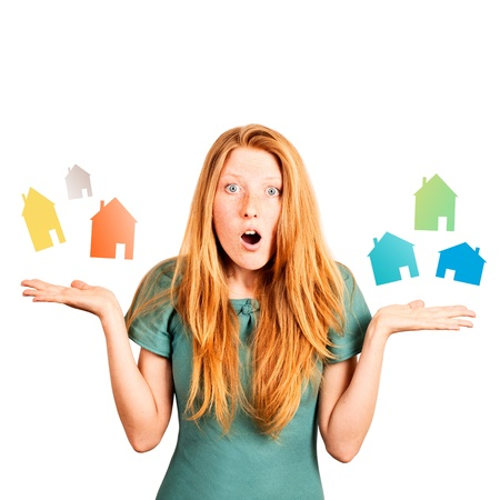 red-haired girl facing a choice isolated on a white, holding coloured houses at her hands  Stock Photo - 20535272