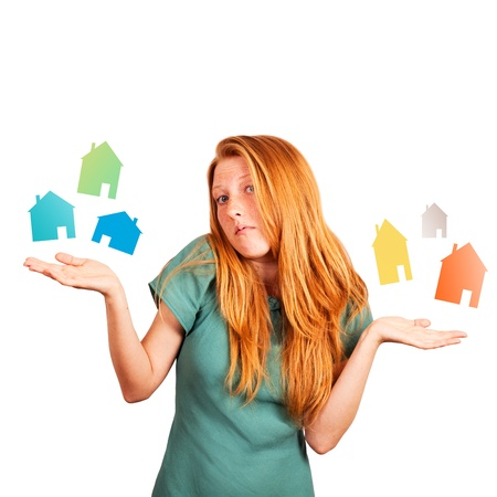 red-haired girl facing a choice isolated on a white, holding coloured houses at her hands