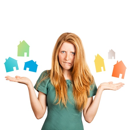 red-haired girl facing a choice isolated on a white, holding coloured houses at her hands  Stock Photo - 20535263