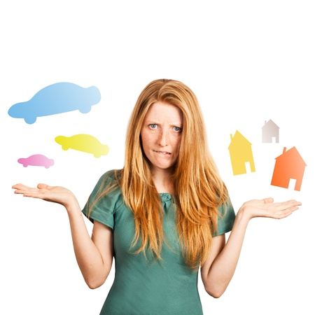 red-haired girl facing a choice isolated on a white, holding coloured cars and houses at her hands  photo