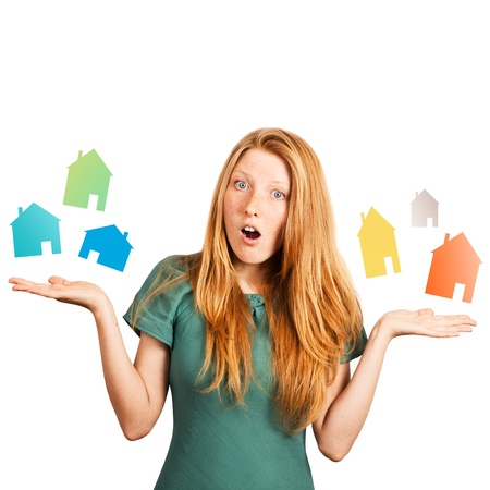 red-haired girl facing a choice isolated on a white, holding coloured houses at her hands  photo