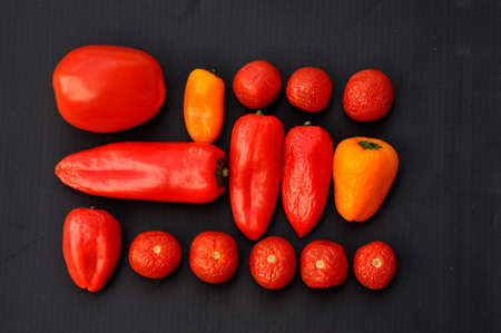 red and orange peppers on black background Stock Photo