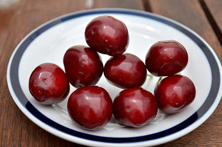 plate with shiny cherries Stock Photo