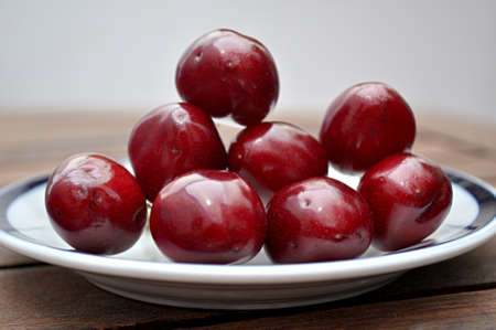 un healthy: plate with shiny cherries Stock Photo