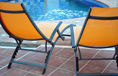 chaise: two chaise lounges poolside