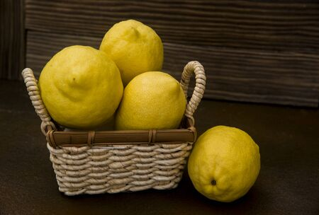 lemons  in a wicker basket on rustic background 스톡 콘텐츠