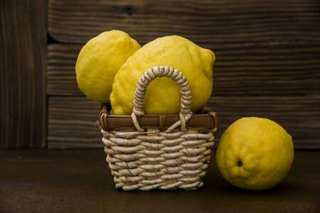 lemons  in a wicker basket on rustic background Фото со стока - 128781836