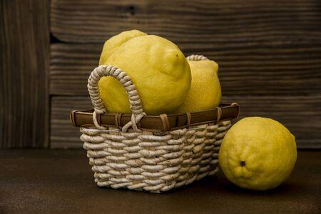 lemons  in a wicker basket on rustic background Фото со стока