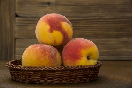 Peaches in a wicker basket on rustic background Фото со стока - 128781846