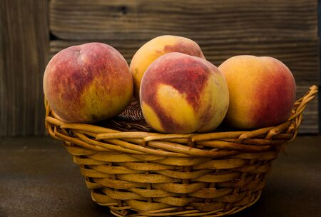 Peaches in a wicker basket on rustic background Фото со стока - 128781847