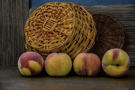 Peaches in a wicker basket on rustic background