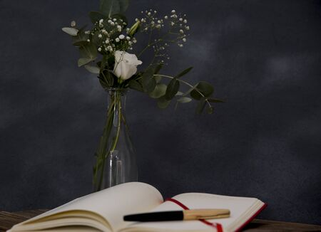 romantic bouquet and note book with pen foreground