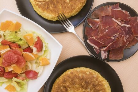 Spanish potato tortillas, ham and grapefruit salad in various dishes