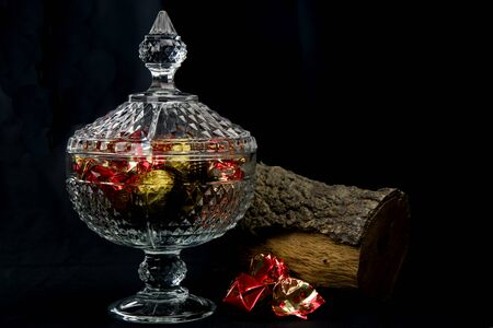 carved glass bonbonniere full of chocolates wrapped in red