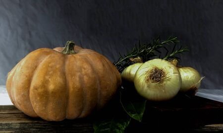 table with pumpkin and sweet onions in a rustic kitchen Zdjęcie Seryjne