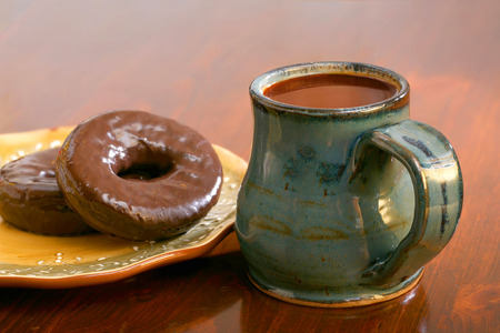 Coffee and chocolate donuts on a plate