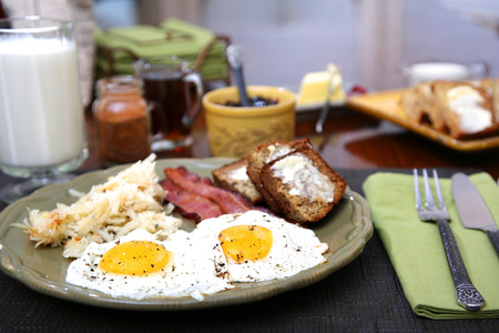 browns: Eggs sunny side up with hash browns bacon strips and banana bread for breakfast