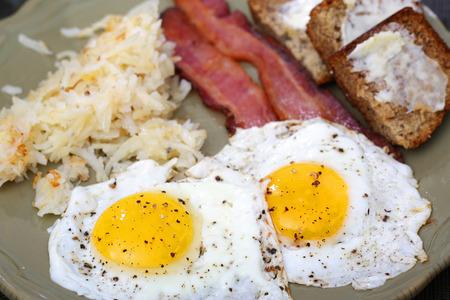 papas doradas: Los huevos soleado hacia arriba con tiras hash browns tocino y pan de plátano para el desayuno