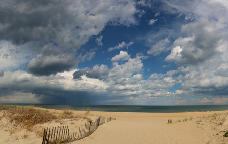 Sandbridge, Virginia sandy beach with fence blue sky clouds on coastline Stock Photo