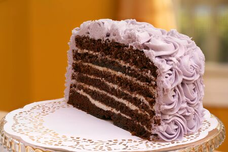 deluxe: Deluxe 6 layer round chocolate butter cream cake with purple frosting and elegant glass stand Stock Photo