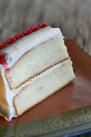 vanilla cake: Piece of white vanilla cake with colorful frosting closeup with select focus