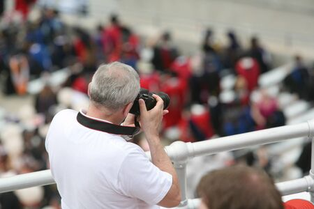 spectator: Spectator taking pictures from balcony at college graduation commencement