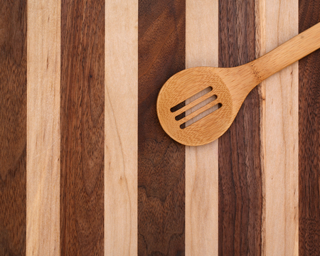 slotted: Slotted wood spoon on cutting board with copy space