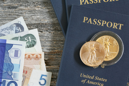 grouping: Grouping of travel related passports gold coins and international paper currency