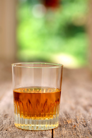 shooter drink: Whiskey in a glass on wooden table with vibrant green outdoors background