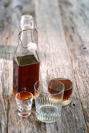 amaretto: Amaretto served in various glasses on rustic wooden table top