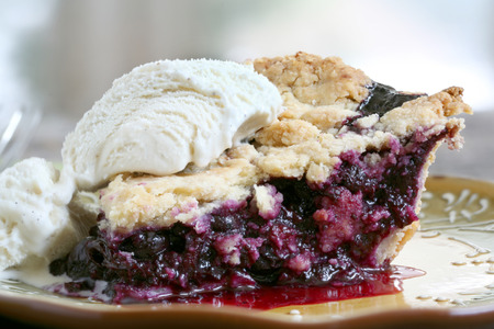 pie: Blueberry pie with ice cream on rustic wooden table with place mat