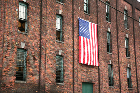 distillers: Distillery brick wall with large american flag Stock Photo