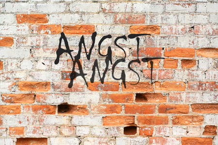 Aged crumbling street wall background with red bricks texture and Angst message
